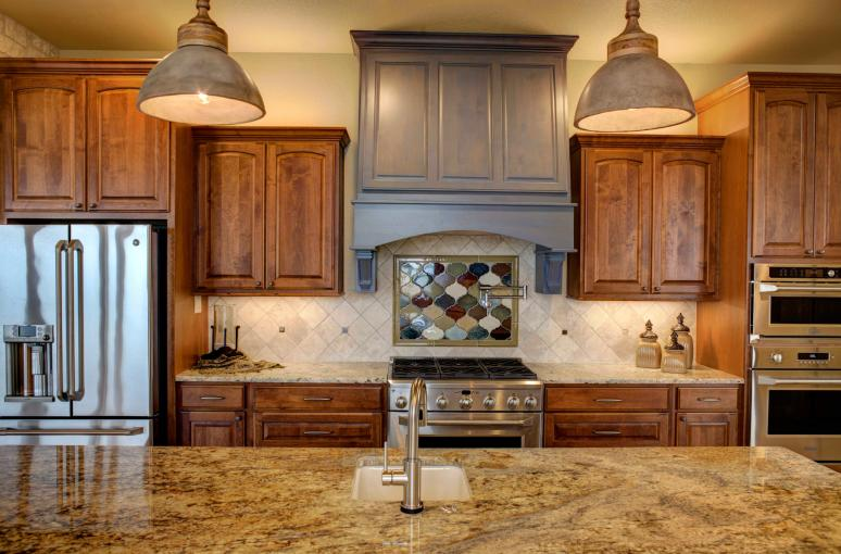The kitchen has customized stained alder cabinets with leather finished granite.